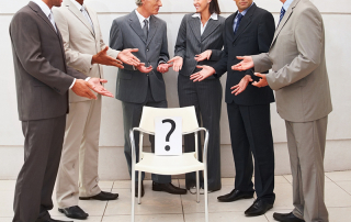 Surprised business people having  discussion over a question mark on chair