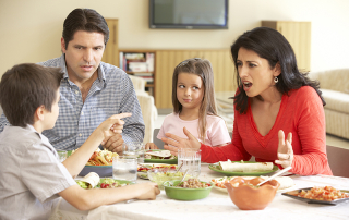 Young Hispanic Family Arguing While Eating Meal Sitting At Dinner Table At Home