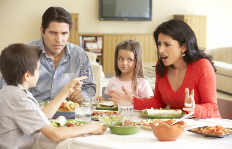Young Hispanic Family Arguing While Eating Meal At Home